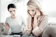 Mulher desapontado deprimida que senta-se fechando suas orelhas fotografia de stock royalty free