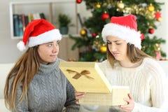 Mulher desapontado que recebe um presente no Natal imagem de stock