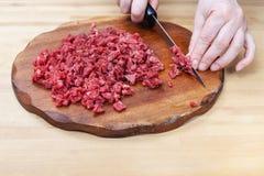 A mulher desbasta finamente a carne na placa de corte Imagens de Stock Royalty Free