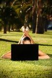 Mulher descalça em uma grama com um portátil Fotos de Stock Royalty Free