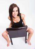 A mulher descalça bonita nova impressionante escarrancha o couro preto Foto de Stock