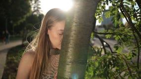 Mulher desesperada que inclina sua cabeça no tronco de árvore filme