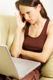 Mulher desgastada com portátil Fotografia de Stock Royalty Free