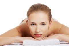 Mulher despida caucasiano bonita que encontra-se em uma tabela e em um rel da massagem imagens de stock royalty free