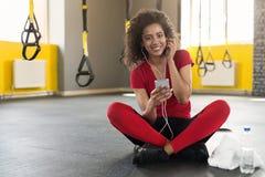 Mulher desportiva afro-americano que escuta a música no smartphone no gym foto de stock royalty free