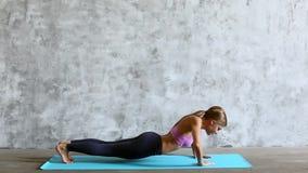 Mulher desportiva apta que faz a flexão de braço na esteira da ioga filme
