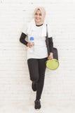 Mulher desportiva asiática que inclina-se contra a parede que descansa após o workou fotografia de stock