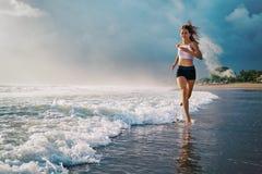 A mulher desportiva ativa corre ao longo da praia do oceano do por do sol Ostenta o fundo imagem de stock royalty free