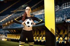 Mulher desportiva atlética no sportswear com a bola de futebol nas mãos no estádio foto de stock