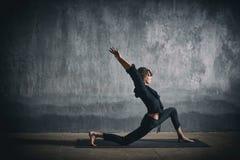 A mulher desportiva bonita do yogini do ajuste pratica o asana Virabhadrasana 1 da ioga - a pose 1 do guerreiro no salão escuro foto de stock royalty free