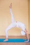 A mulher desportiva bonita do yogini do ajuste pratica o chakrasana do pada do eka do asana da ioga (ou o dhanurasana do urdva do imagem de stock royalty free