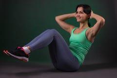 Mulher desportiva bonita, mulher da aptidão que faz o exercício em um fundo escuro com luminoso verde Fotografia de Stock Royalty Free