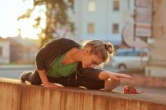 Mulher desportiva bonita que faz esticando o exercício fora Foto de Stock