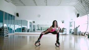 Mulher desportiva bonita que faz os exercícios em sapatas do kangoo vídeos de arquivo