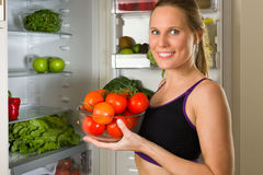 Mulher desportiva, caucasiano que mostra vegetais para comer saudável Imagens de Stock Royalty Free