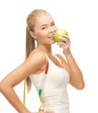 Mulher desportiva com maçã e a fita de medição imagem de stock royalty free