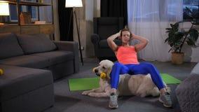 Mulher desportiva com o cão de estimação que faz o exercício de sentar-UPS video estoque