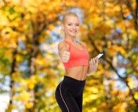 Mulher desportiva de sorriso com smartphone Fotos de Stock Royalty Free