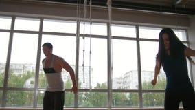 A mulher desportiva e o instrutor muscular da aptidão do homem que fazem a caixa saltam o exercício durante um exercício no gym filme