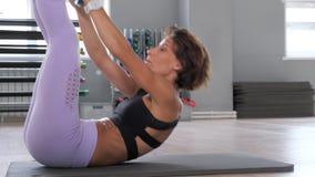 A mulher desportiva está fazendo o Abs tritura com o disco verde do peso livre na esteira vídeos de arquivo