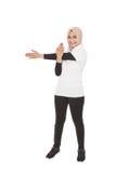Mulher desportiva muçulmana que faz a mão que estica ao sorrir imagem de stock