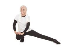 Mulher desportiva muçulmana que faz o esticão do pé fotografia de stock royalty free