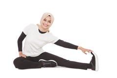 Mulher desportiva muçulmana que faz o esticão do pé imagem de stock