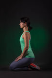 Mulher desportiva, mulher da aptidão que senta-se em um fundo escuro com luminoso verde Fotografia de Stock