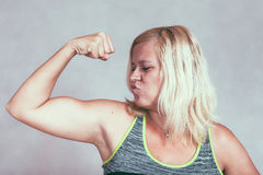 Mulher desportiva muscular forte que dobra o bíceps imagens de stock