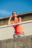 Mulher desportiva na chamada do smartphone imagens de stock