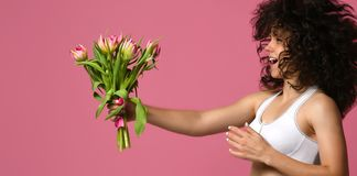 mulher desportiva no sportswear com as tulipas das flores nas m?os em um fundo cor-de-rosa imagens de stock royalty free