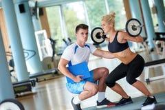 Mulher desportiva nova com levantamento de pesos do exercício do instrutor Imagens de Stock Royalty Free