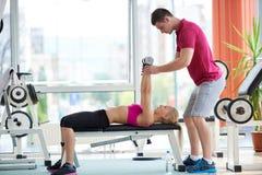 Mulher desportiva nova com levantamento de pesos do exercício do instrutor Fotos de Stock