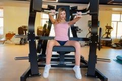 A mulher desportiva nova faz o exerc?cio da imprensa do ombro no gym moderno imagens de stock