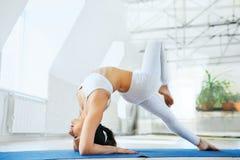 Mulher desportiva nova na ioga praticando do sportswear branco no est?dio da ioga com fundo branco da parede Estilo de vida saud? fotos de stock royalty free