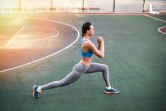 Mulher desportiva nova no sportswear que exercita no estádio foto de stock