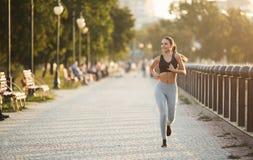 Mulher desportiva nova que corre no cais no parque da cidade fotos de stock