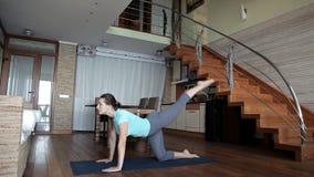 Mulher desportiva nova que dá certo em casa, fazendo exercícios da aptidão no assoalho da sala de visitas usando o treinamento pe vídeos de arquivo
