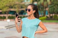 Mulher desportiva nova que descansa após o exercício usando seu smartphone e escutando a música nos fones de ouvido Corredor do a imagens de stock royalty free