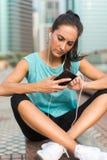 Mulher desportiva nova que descansa após o exercício usando seu smartphone e escutando a música nos fones de ouvido Corredor do a imagens de stock