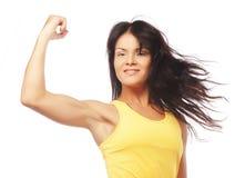 Mulher desportiva nova que dobra seu bíceps foto de stock