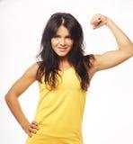 Mulher desportiva nova que dobra seu bíceps fotografia de stock