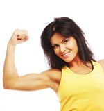 Mulher desportiva nova que dobra seu bíceps imagens de stock