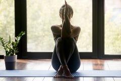 Mulher desportiva nova que faz o exercício de braços de Garudasana foto de stock