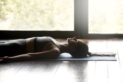 Mulher desportiva nova que relaxa na pose de Savasana imagem de stock