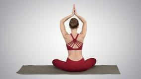A mulher desportiva nova que senta-se na pose dos lótus, junta-se às mãos acima de sua cabeça no fundo do inclinação video estoque