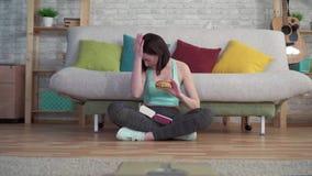 Mulher desportiva nova que senta-se no assoalho que olha as escalas de banheiro que comem um hamburguer video estoque