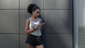 Mulher desportiva nova que usa um smartphone filme