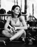 A mulher desportiva nova tem uma ruptura no treinamento no gym faz uma banana do petisco imagem de stock