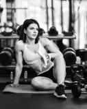 A mulher desportiva nova tem uma ruptura no treinamento no gym faz uma banana do petisco imagens de stock royalty free